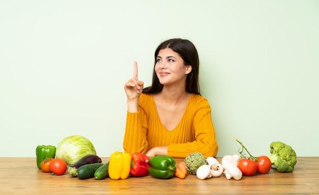 Fille adolescente avec beaucoup de légumes montrant et en levant un doigt en signe du meilleur