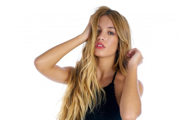 Fille adolescente blonde toucher les cheveux sur blanc