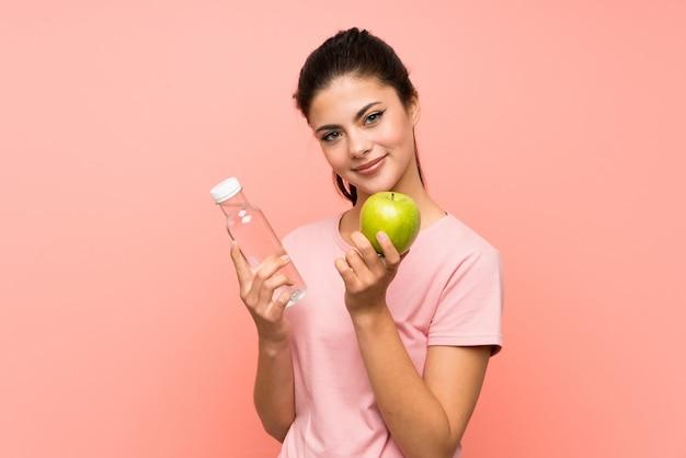 Fille adolescente avec une bouteille d'eau et une pomme