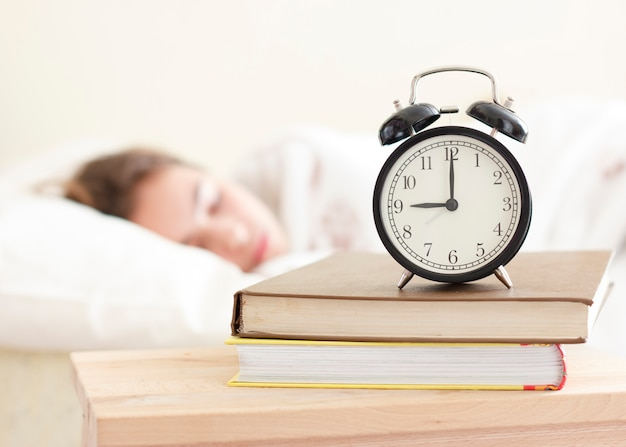 Fille adolescente dormant dans un lit blanc. réveil au premier plan sur une pile de livres