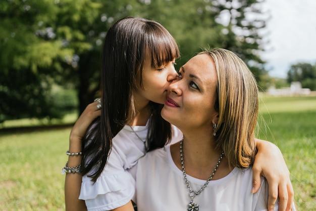 Fille Adolescente Embrassant Sa Mère à L'extérieur. Photo Premium