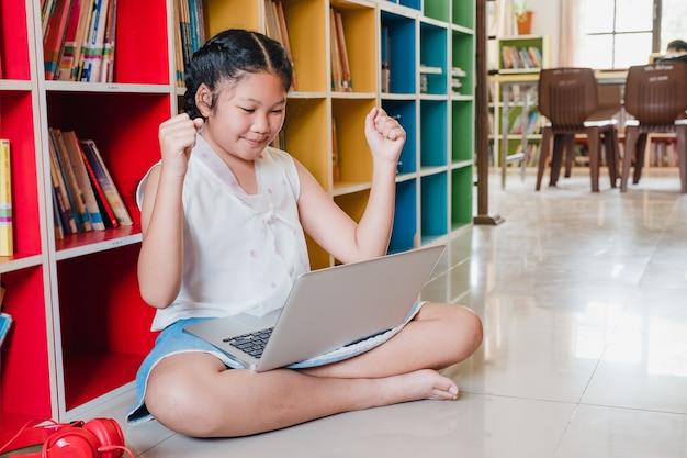 Fille adolescente étudiant célébrer avec un ordinateur portable pour l'éducation à l'école.