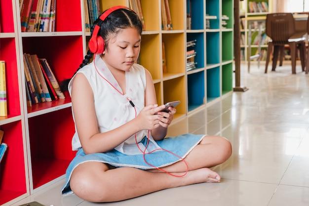 Fille adolescente étudiant en utilisant un téléphone intelligent pour l'éducation à l'école.