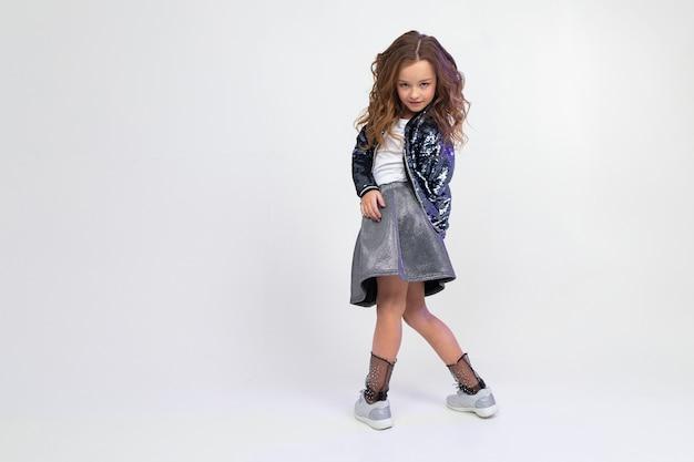 Fille adolescente européenne d'une belle manière dansant en pleine croissance sur un fond de studio léger avec espace de copie.