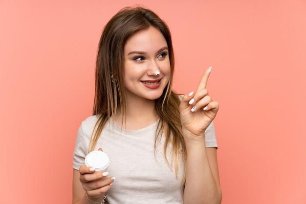 Fille adolescente sur fond rose avec crème hydratante