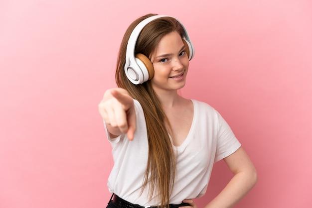 Fille adolescente sur fond rose isolé, écouter de la musique