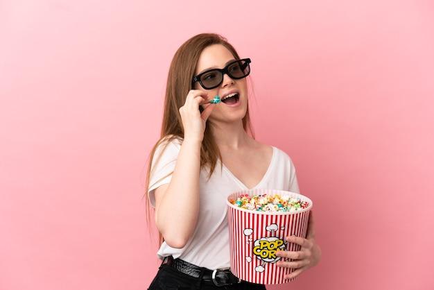 Fille adolescente sur fond rose isolé avec des lunettes 3d et tenant un grand seau de pop-corn