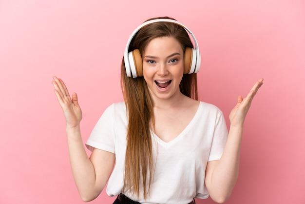 Fille adolescente sur fond rose isolé surpris et écouter de la musique
