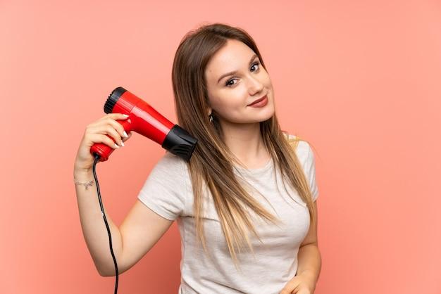 Fille adolescente sur fond rose avec sèche-cheveux