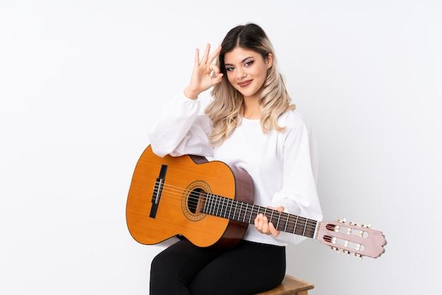 Fille adolescente avec guitare sur blanc isolé montrant un signe ok avec les doigts