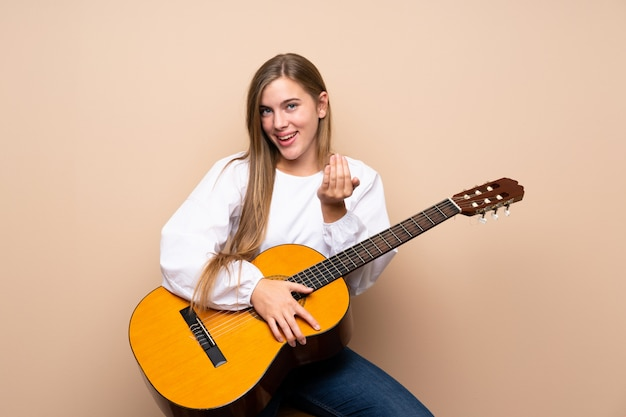 Fille adolescente avec guitare invitant à venir avec la main. heureux que tu sois venu