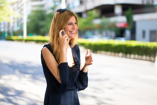 Fille adolescente heureuse jeune et jolie parlant au téléphone dans la rue