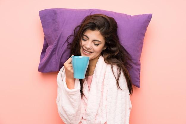 Fille adolescente heureuse en robe de chambre sur fond rose et tenant une tasse de café