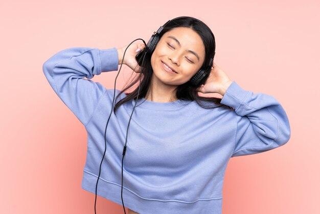 Fille adolescente isolée sur la musique d'écoute rose