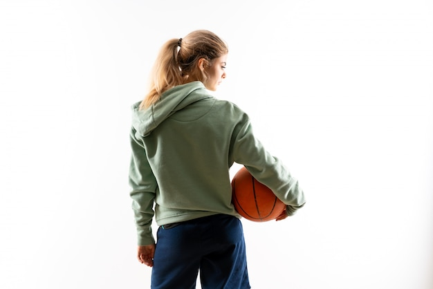 Fille adolescente jouant au basket isolé blanc