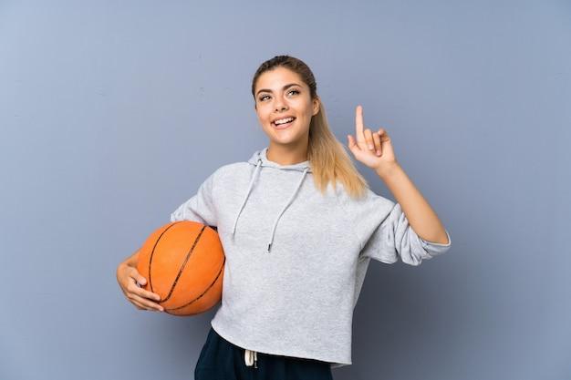 Fille adolescente jouant au basketball sur un mur gris pointant vers le haut une excellente idée