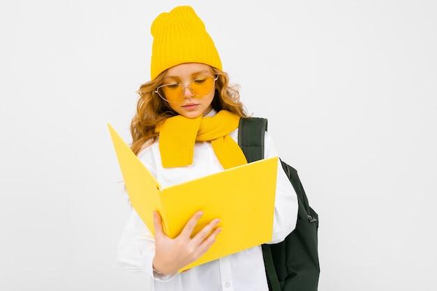 Fille adolescente avec des livres à la main et un sac à dos sur ses épaules sur un fond blanc isolé.