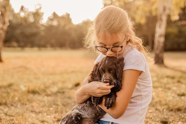 Fille adolescente avec des lunettes jouant sur l'herbe avec son petit chien, chiot cocker brun, à l'extérieur, dans un parc.