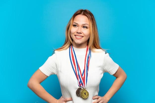 Fille adolescente avec des médailles sur fond isolé posant avec les bras à la hanche et souriant