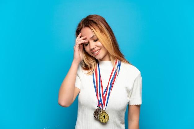 Fille adolescente avec des médailles sur fond isolé en riant