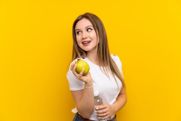 Fille adolescente sur un mur jaune avec une pomme et une bouteille d'eau