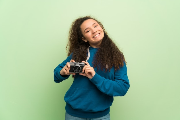 Fille adolescente sur mur vert tenant une caméra