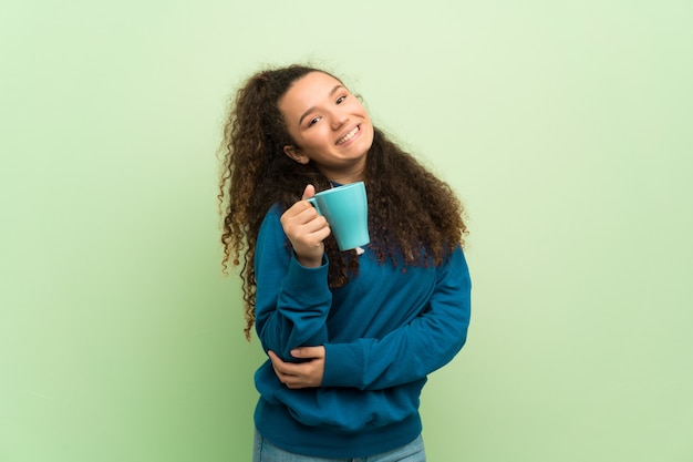 Fille adolescente sur mur vert, tenant une tasse de café