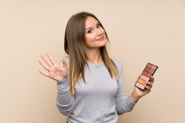 Fille adolescente avec palette de maquillage sur fond isolé, saluant avec main avec expression heureuse