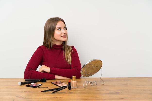 Fille adolescente avec palette de maquillage et produits de beauté dans une table à la recherche sur le côté