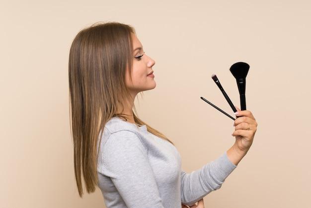 Fille adolescente avec un pinceau de maquillage sur un mur isolé