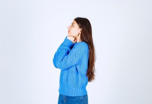 Fille adolescente en pull bleu pensant à quelque chose sur le blanc.