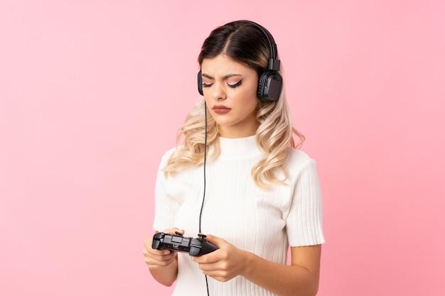 Fille adolescente sur rose isolé jouant aux jeux vidéo