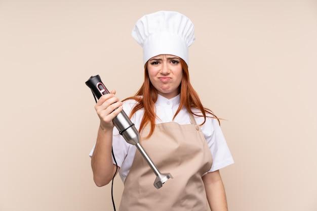 Fille adolescente rousse à l'aide d'un mélangeur à main sur un mur isolé avec une expression triste