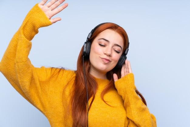 Fille adolescente rousse sur bleu écoute de la musique et de la danse