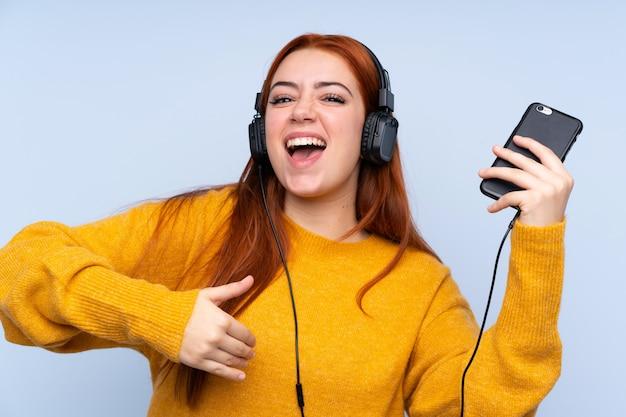Fille adolescente rousse sur bleu écouter de la musique et faire un geste de guitare