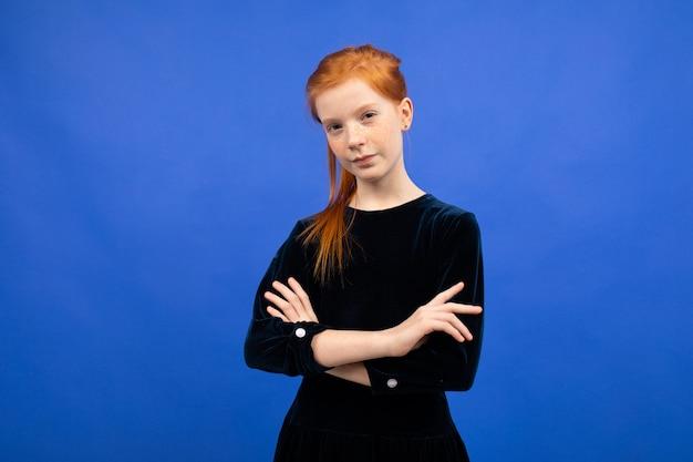 Fille adolescente rousse grave avec les bras croisés sur un bleu