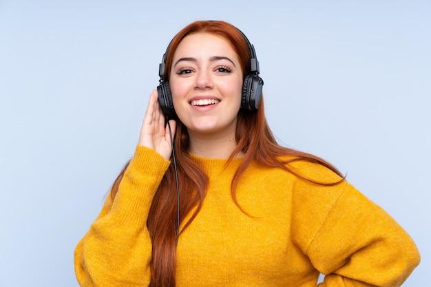Fille adolescente rousse sur la musique d'écoute de mur bleu isolé