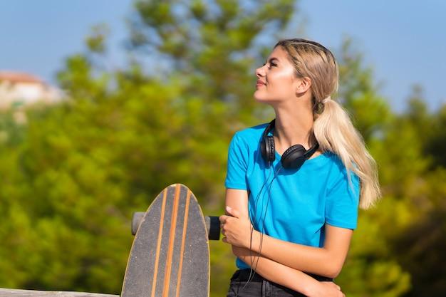 Fille adolescente avec skate au plein air heureux et souriant