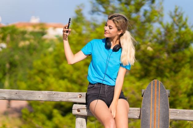 Fille adolescente avec skate à l'extérieur faisant un selfie