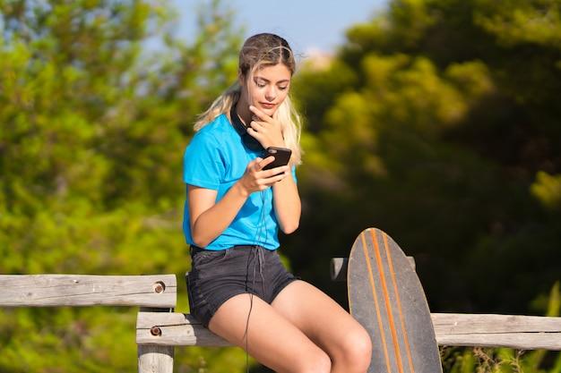 Fille adolescente avec skate à l'extérieur surpris et envoyant un message
