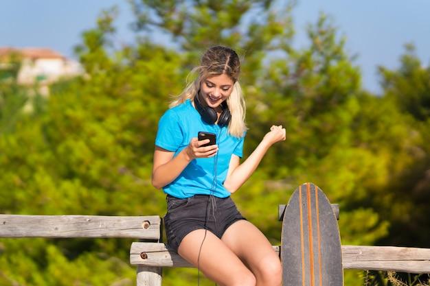 Fille adolescente avec skate à l'extérieur avec téléphone en position de victoire