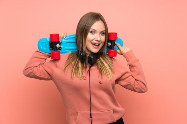 Fille adolescente avec skate sur fond rose isolé