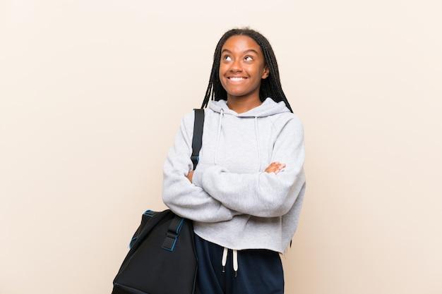 Fille adolescente de sport afro-américain avec de longs cheveux tressés, levant tout en souriant