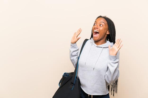 Fille adolescente sportive afro-américaine avec de longs cheveux tressés avec une expression faciale surprise