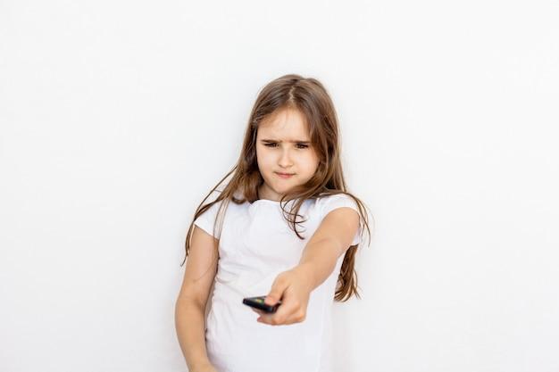Une fille, une adolescente avec une télécommande de la télévision, change de chaîne, recherche un dessin animé, n'est pas heureuse, interdiction de regarder, enfants et adultes, télévision et internet, divertissement