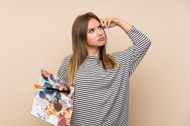 Fille adolescente tenant une palette sur un mur isolé ayant des doutes et avec une expression de visage confuse