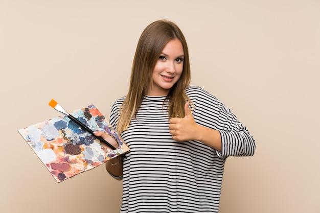 Fille adolescente tenant une palette sur un mur isolé donnant un geste du pouce