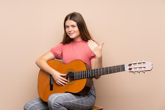 Fille adolescente ukrainienne avec guitare invitant à venir avec la main. heureux que tu sois venu