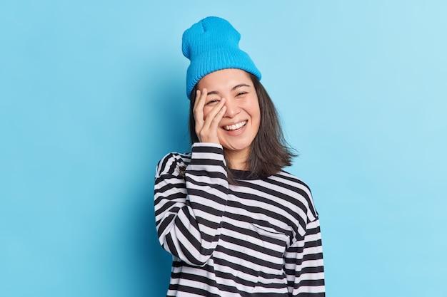 Une fille adorable brune positive avec une apparence orientale couvre le visage avec la main sourit joyeusement