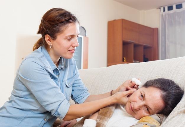 Fille adulte dégoulinant des gouttes d'oreille à la mère mûre